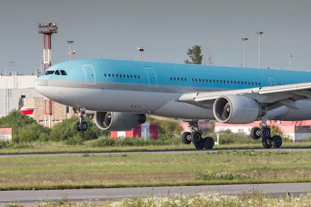 Nahaufnahme der modernen passagierflugzeuglandung mit aufsetzen auf der landebahn am flughafen