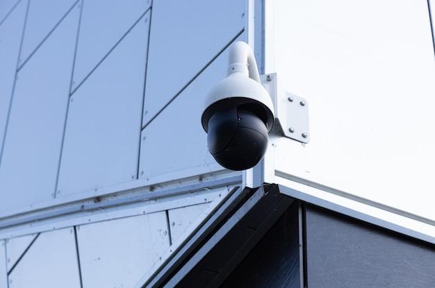 Nahaufnahme der modernen videoüberwachungskamera auf weißem gebäude