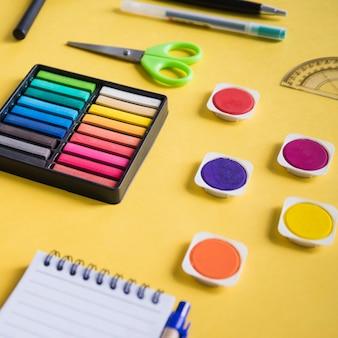 Nahaufnahme der multi farbigen aquarellfarbe und der schreibwaren auf gelbem hintergrund