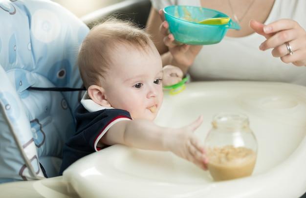 Nahaufnahme der mutter, die baby mit brei füttert
