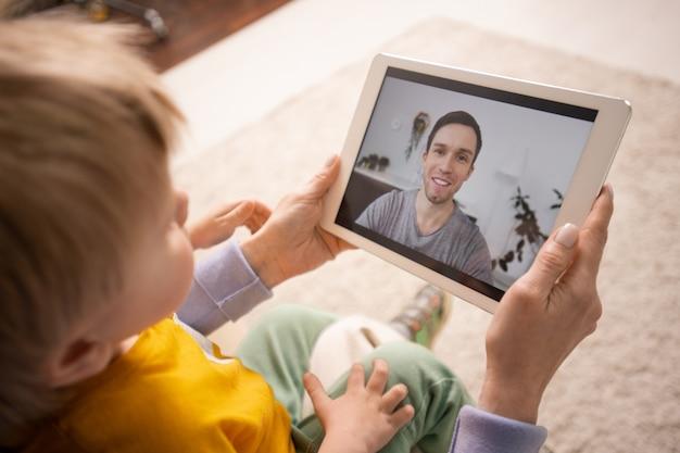 Nahaufnahme der mutter, die tablette hält und sohn zeigt, während vater über videokonferenz-app verbindet