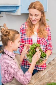 Nahaufnahme der mutter und der tochter, die den salat zubereiten
