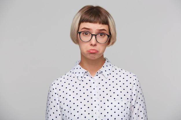 Nahaufnahme der nachdenklichen hübschen blonden jungen frau trägt tupfenhemd