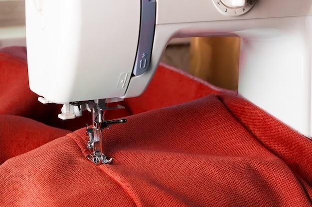 Nahaufnahme der nähmaschine, die mit rotem stoff arbeitet