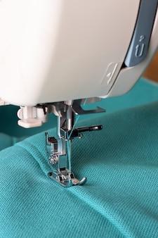 Nahaufnahme der nähmaschine, die mit türkisfarbenem stoff arbeitet