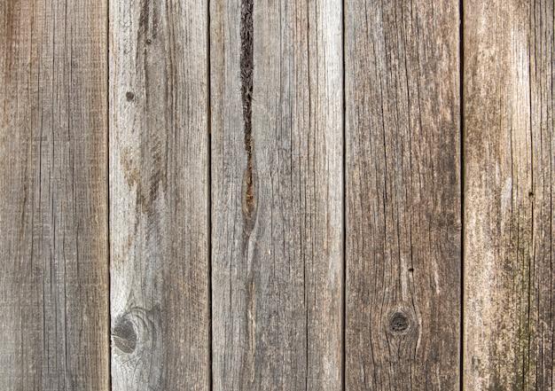 Nahaufnahme der natürlichen alten weinlese verwitterte grauen braunen unbemalten festen bretterzaun oder tor von planken und von brettern. sonniger geknisterter hintergrund des vertikalen kopienraumes der ökologischen beschaffenheit.