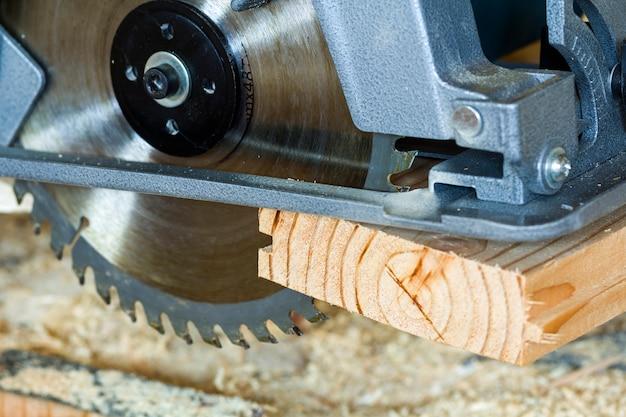 Nahaufnahme der neuen modernen starken elektrischen kreissäge, die hölzerne planken schneidet. tischlerwerkzeug, bau, reparatur und gebäudekonzept.
