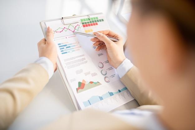 Nahaufnahme der nicht erkennbaren beschäftigten frau, die mit stift auf liniendiagramm zeigt, während informationen im bericht untersucht