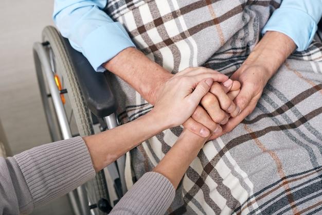 Nahaufnahme der nicht erkennbaren frau, die hände des älteren mannes hält, der unter decke im rollstuhl sitzt