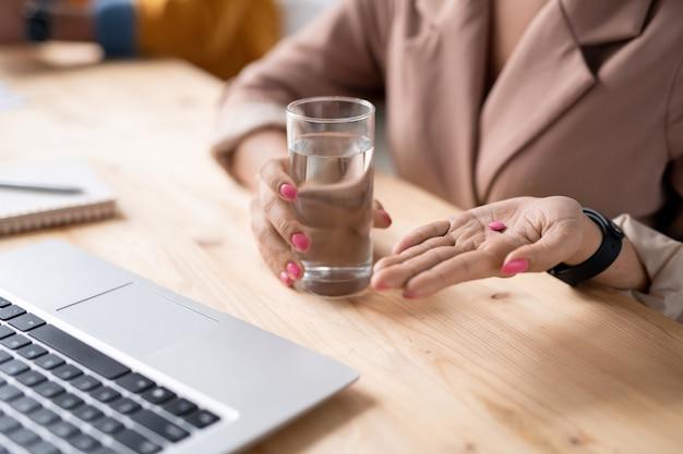 Nahaufnahme der nicht erkennbaren geschäftsfrau, die glas wasser hält und rosa pille am arbeitsplatz nimmt