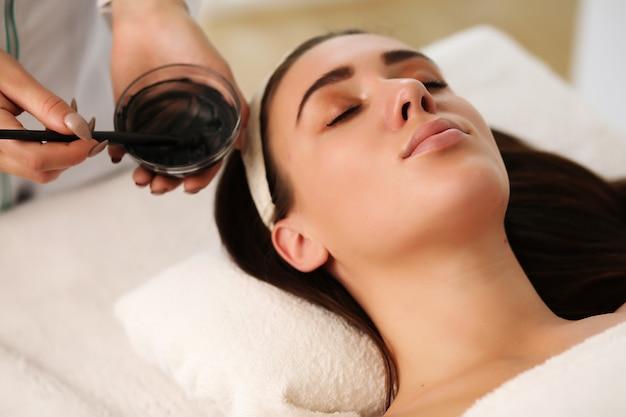 Nahaufnahme der nicht erkennbaren kosmetikerin, die gesichtsmaske mit pinsel auf gesicht der schönen frau anwendet, die auf massagetisch im spa-zentrum liegt
