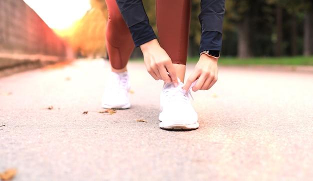 Nahaufnahme der nicht erkennbaren sportfrau, die sportschuhe während des abendlaufs im freien bindet.