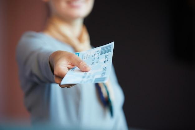 Nahaufnahme der nicht erkennbaren weiblichen flugbegleiterin, die dem passagier tickets gibt, während sie am check-in-schalter im flughafen steht,