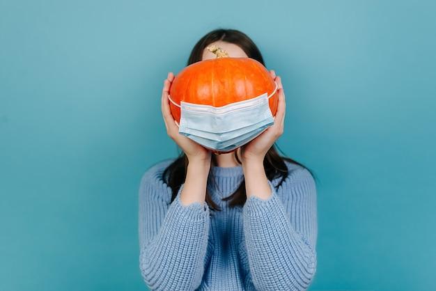 Nahaufnahme der nicht wiedererkennbaren jungen frau halten halloween-kürbis in einer schützenden medizinischen maske