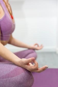 Nahaufnahme der nicht wiedererkennbaren person, die yoga in der meditationshaltung praktiziert. vertikale ansicht. platz für text.