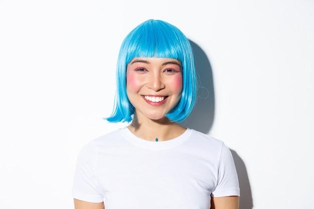 Nahaufnahme der niedlichen asiatischen frau, die halloween in der blauen perücke feiert, glücklich lächelnd an der kamera, stehend.