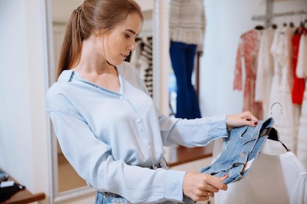 Nahaufnahme der niedlichen jungen frau, die kleidung im bekleidungsgeschäft denkt und wählt