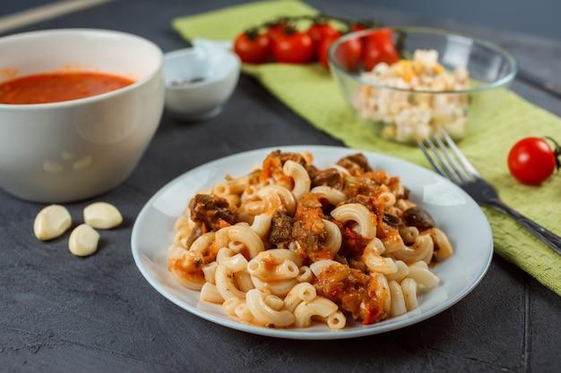Nahaufnahme der nudeln mit fleisch und tomatensauce in der front. tomatensuppe und bunter salat