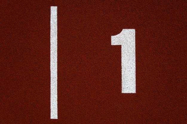 Nahaufnahme der nummer eins auf der roten stadionlaufbahn