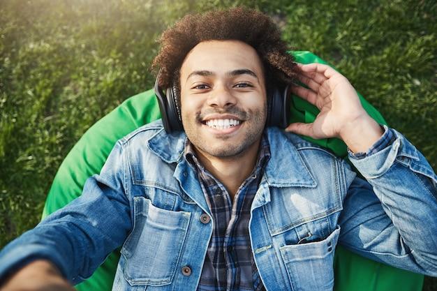 Nahaufnahme der oberen ansichtaufnahme des hübschen afrikanischen mannes mit afro-frisur, die hand in richtung kamera ausdehnt, während musik über kopfhörer hört, im park im jeansmantel liegend und lächelnd.