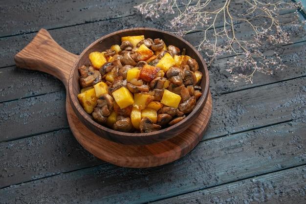Nahaufnahme der oberen seite schüssel mit heißem gericht holzschüssel mit kartoffeln und pilzen auf dem schneidebrett auf der dunklen oberfläche neben den ästen