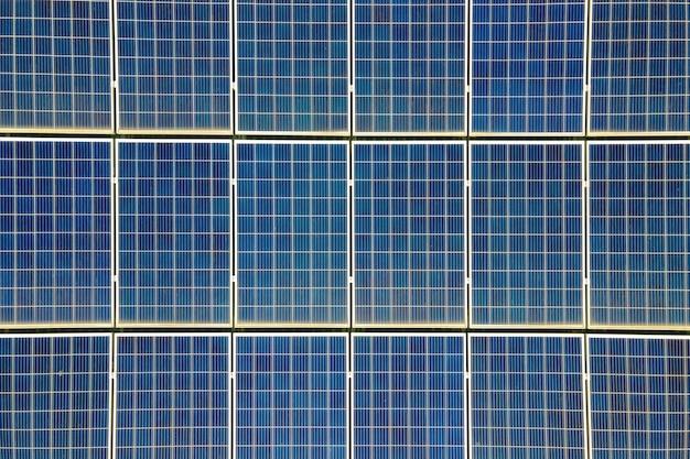 Nahaufnahme der oberfläche von blauen photovoltaik-sonnenkollektoren, die auf dem dach des gebäudes montiert sind, um sauberen ökologischen strom zu produzieren. produktion eines erneuerbaren energiekonzepts.