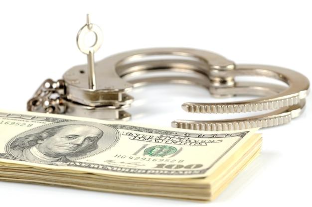 Nahaufnahme der offenen metallhandschellen, der schlüssel und des stapels des amerikanischen dollars bargeld lokalisiert über weißem hintergrund. illegale geldverdienungs-, bestechungs- und korruptionsserien