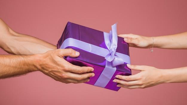Nahaufnahme der paarholding wickelte purpurrote geschenkbox gegen farbigen hintergrund ein