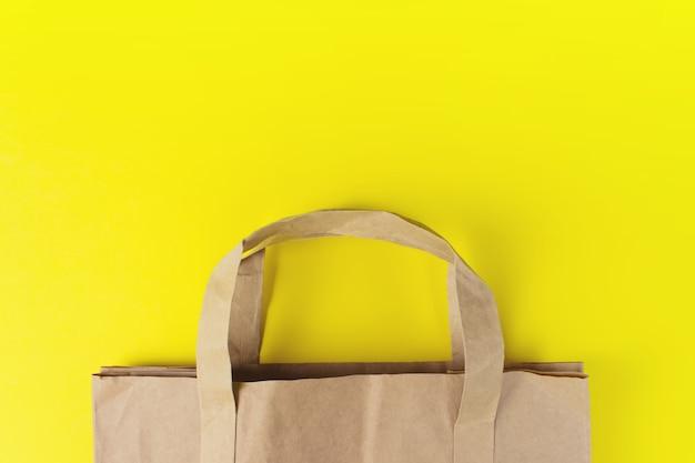 Nahaufnahme der papiertüte über gelbem hintergrund mit kopienraum. flaches laienfoto von leeren einkäufen