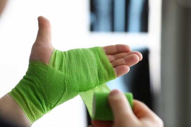 Nahaufnahme der person bindet hand mit grünem assverband. knochenbruch und röntgenbild des bruchhandgelenks. verletzung oder unfall