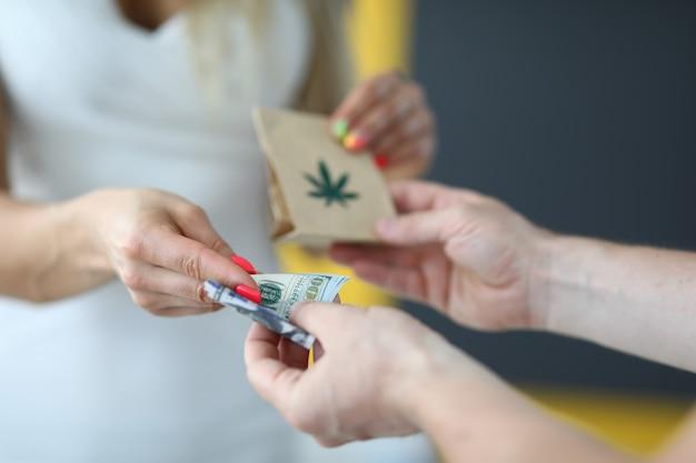 Nahaufnahme der person, die paket mit cannabiszeichen kauft. mann, der geldbanknoten für medikamente gibt