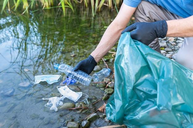 Nahaufnahme der person, die plastik vom fluss sammelt. mann, der fluss von kunststoffen reinigt. umweltkonzept.