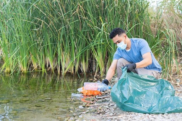 Nahaufnahme der person, die plastik vom fluss sammelt. mann, der fluss von kunststoffen reinigt.