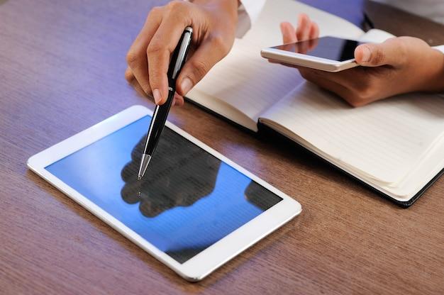 Nahaufnahme der person tablette und smartphone arbeitend und verwendend