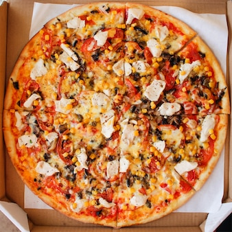Nahaufnahme der pizza mit huhn, tomaten, mais, käse, pilzen und gewürzen. ansicht von oben.