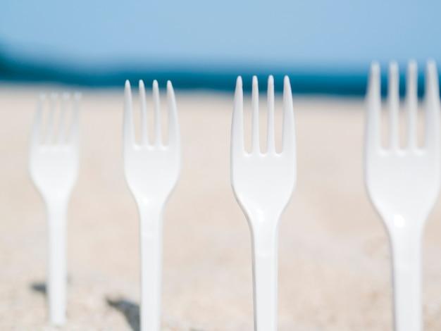 Nahaufnahme der plastikgabeln fest im sand auf dem strand