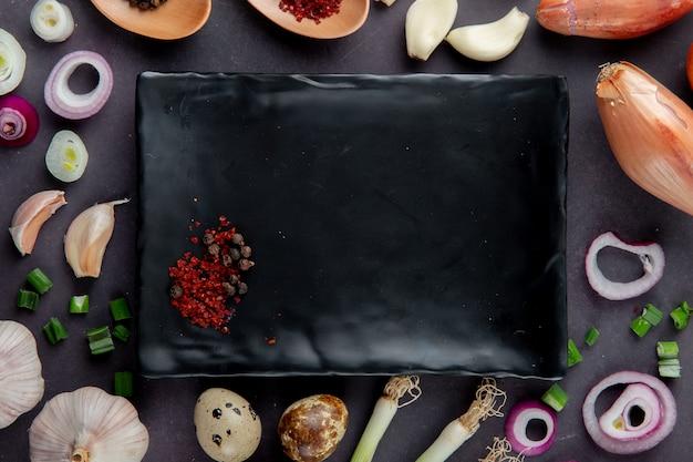Nahaufnahme der platte mit gewürzen und gemüse herum als zwiebelknoblauch-frühlingszwiebel auf kastanienbraunem hintergrund