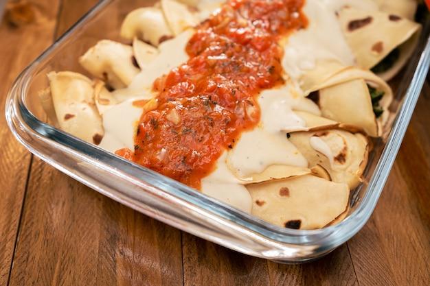 Nahaufnahme der quelle hausgemachter spinat-cannelloni mit bhamelsoße und filet. konzept der hausmannskost, gesundes essen.