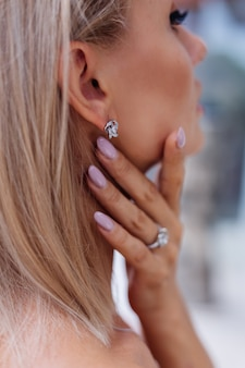Nahaufnahme der reichen luxusfrau im kleid hand und ohr tragen ohrringe und ring am finger