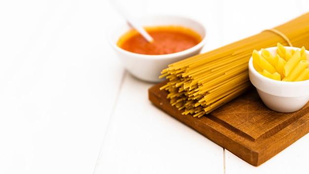 Nahaufnahme der rohen ungekochten teigwaren und der tomatensauce