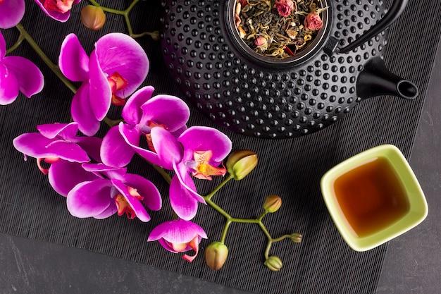 Nahaufnahme der rosa orchideenblume und des trockenen kräutertees auf platzmatte