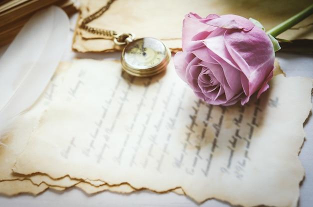 Nahaufnahme der rosenblume mit antiker taschenuhr und liebesbriefen mit weinlese-ton