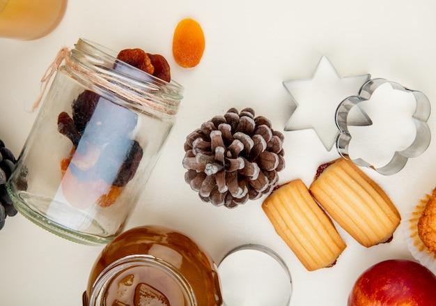 Nahaufnahme der rosinen, die aus glas und tannenzapfen mit pfirsichmarmelade und keksen auf weißem tisch verschüttet werden