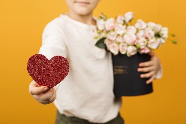 Nahaufnahme der roten herzform in der hand. liebe und valentinstag feiern konzept. kleiner junge, der rote herzform und rosa rosen in seinen händen hält.