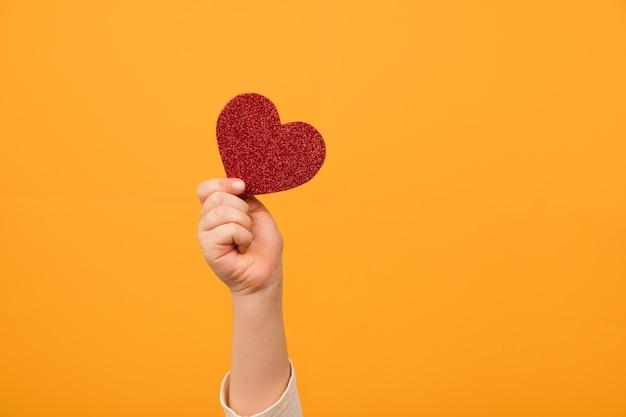 Nahaufnahme der roten herzform in der hand. liebe und valentinstag feiern konzept.