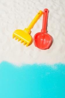 Nahaufnahme der roten schaufel und des gelben rechen auf sand.
