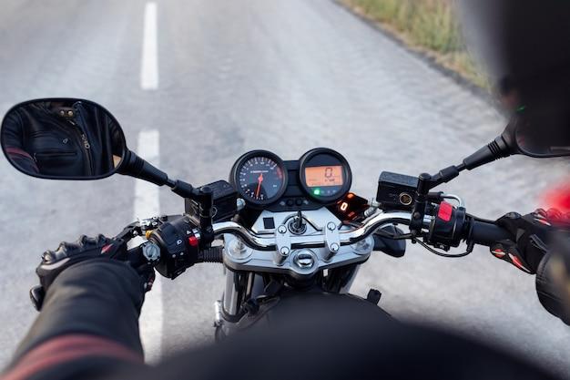 Nahaufnahme der rückansicht des fahrers, der motorrad auf der asphaltstraße fährt.