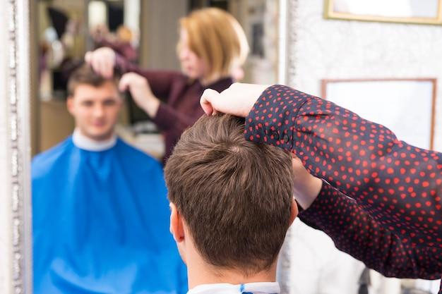 Nahaufnahme der rückansicht des jungen mannes mit haarschnitt und styling von stylist im salon mit unscharfer reflexion im hintergrundspiegel