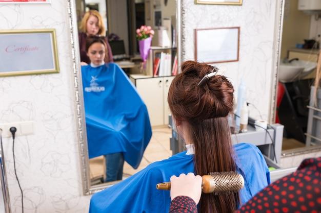 Nahaufnahme der rückansicht des stylisten, der langes haar eines brünetten kunden bürstet, der eine rundbürste im salon mit unscharfer reflexion im großen spiegel im hintergrund verwendet