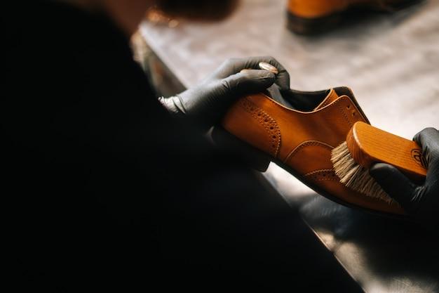 Nahaufnahme der rückansicht eines nicht erkennbaren schusters, der mit alten hellbraunen lederschuhen der bürste putzt
